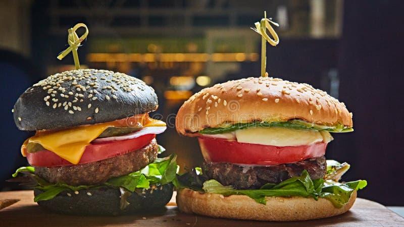 Reeks eigengemaakte burgers in zwart-witte broodjes met tomaat, sla, kaas, ui op houten dienende raad over dark royalty-vrije stock afbeeldingen