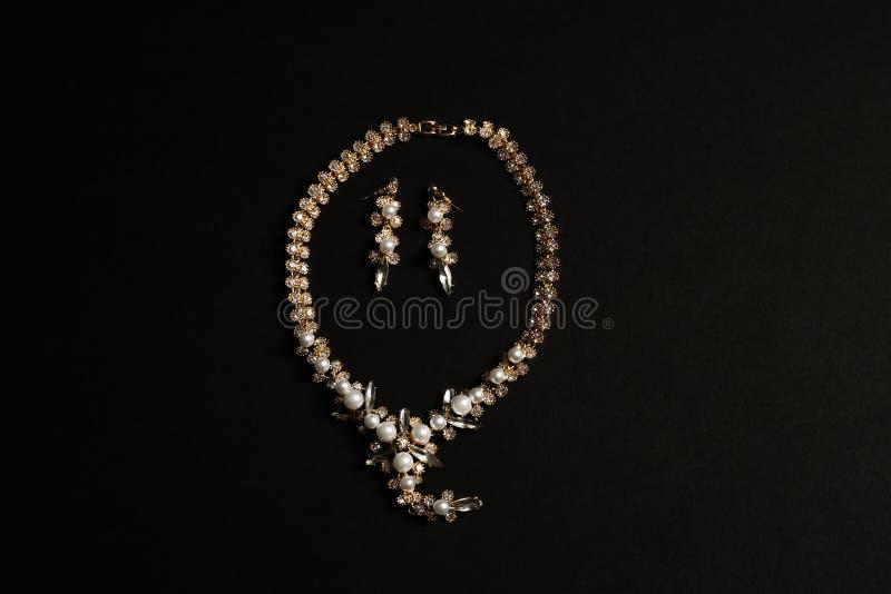 Reeks elegante halsband en oorringen op zwarte achtergrond Luxejuwelen stock fotografie