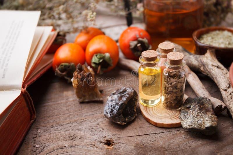 Reeks flessen, assortiment van droge gezonde kruiden, oude boeken, stenen en heksenbehandeling op uitstekend houten bureau royalty-vrije stock afbeeldingen
