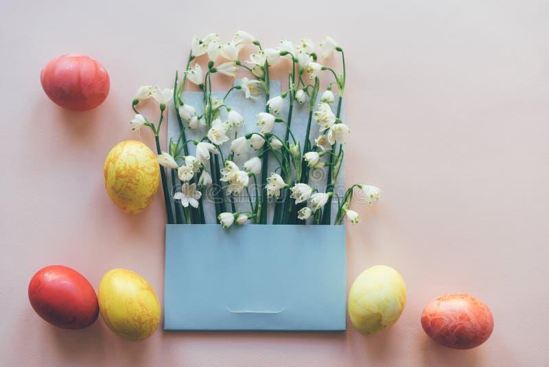 Reeks gekleurde eieren en bloemen in de envelop royalty-vrije stock afbeeldingen