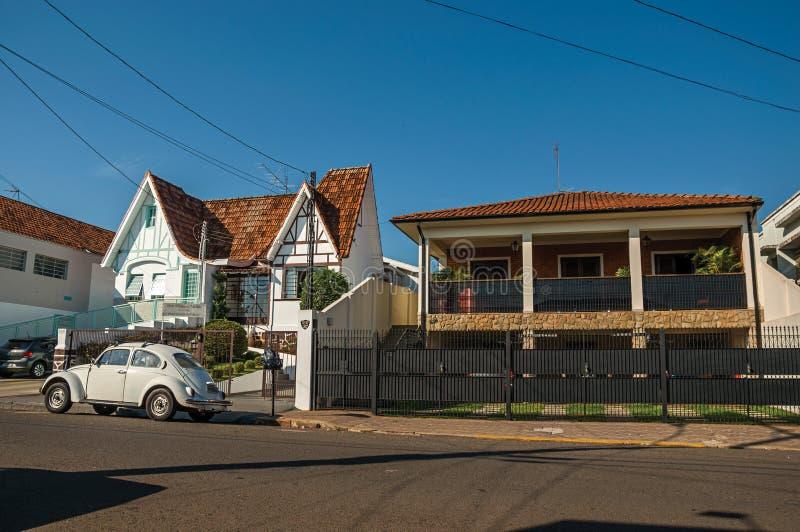 Reeks huizen in stille die straat met een Keverauto vooraan, op een zonnige dag in São Manuel wordt geparkeerd royalty-vrije stock fotografie