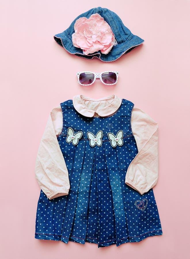 Reeks kleren van de zomerkinderen op roze achtergrond De manier van het babymeisje kijkt met denimkleding, overhemd, hoed en glaz stock foto's