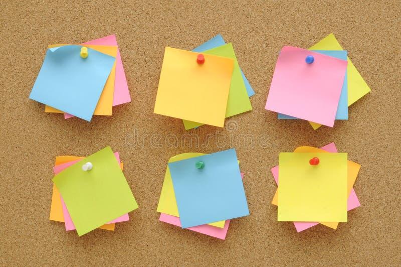 6 reeks kleurrijk van de kleverige spelden van de nota'sduw op cork raad stock foto