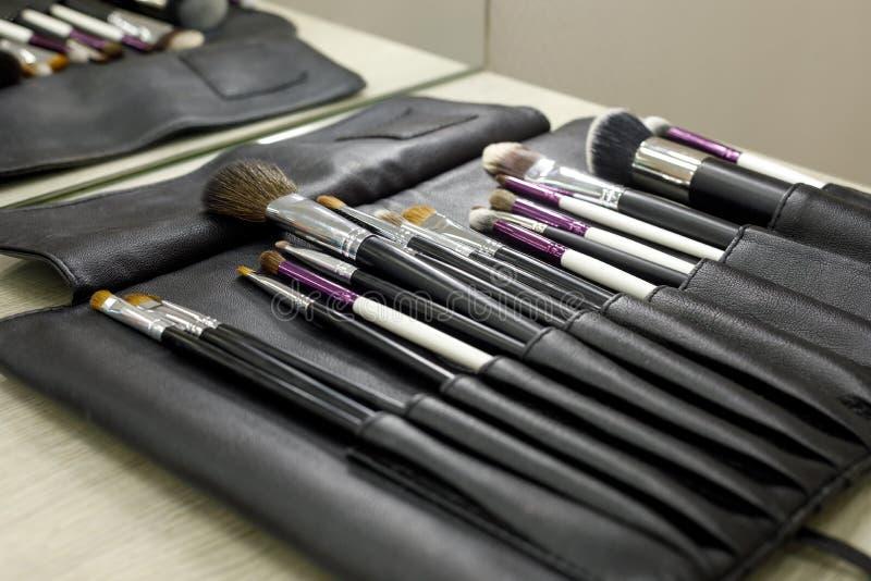 Reeks kosmetische borstels in een zwart leergeval stock fotografie