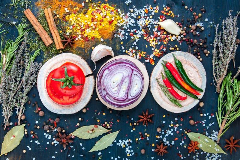 Reeks kruiden en kruiden op houten blauwe achtergrond met tomaat, ui knoflook, peper stock afbeeldingen