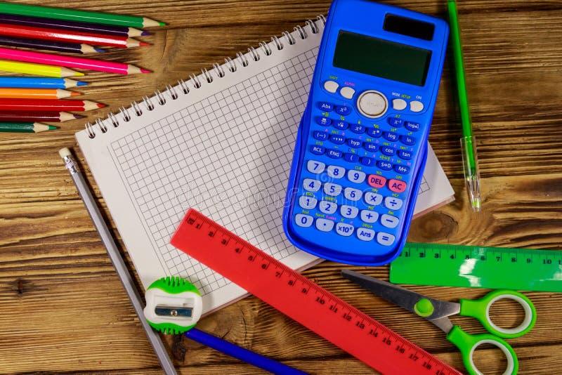 Reeks levering van de schoolkantoorbehoeften Lege blocnote, calculator, heersers, potloden, pennen, schaar en slijper op houten b royalty-vrije stock foto