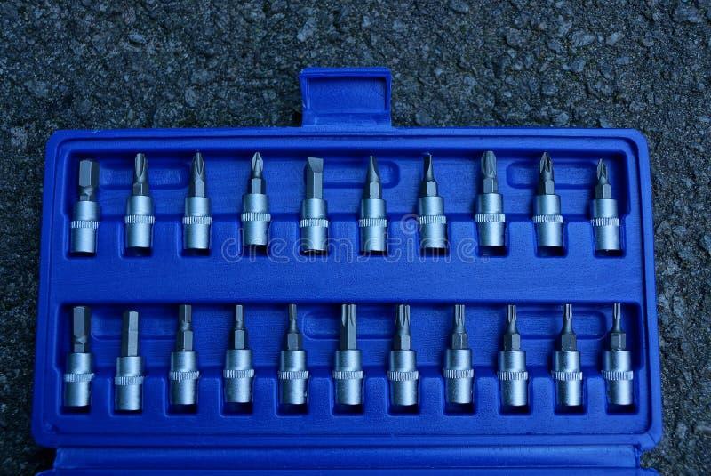 Reeks metaalbeetjes voor een schroevedraaier in een blauwe plastic doos op asfalt royalty-vrije stock foto's