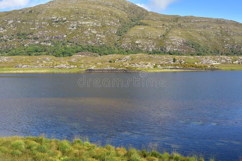 Reeks mountains in Killarney. Calm water of lake near Reeks mountain range in Kerry royalty free stock photography