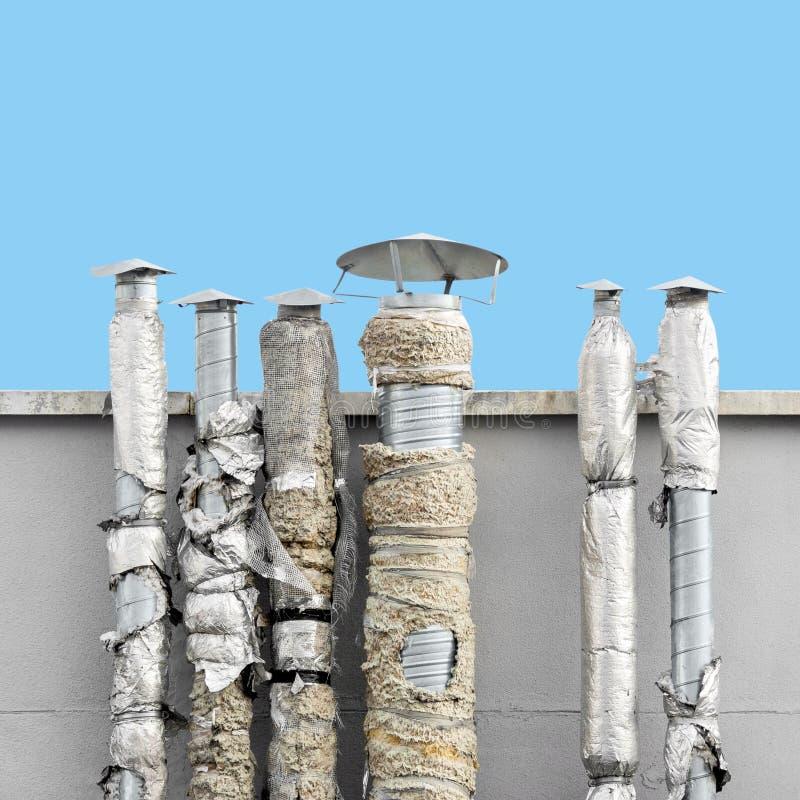 Reeks oude ventilatieschoorstenen tegen blauwe hemel stock afbeelding
