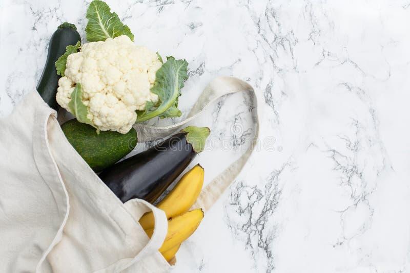 Reeks producten in een katoenen ecozak op een marmeren lijst, bananen, royalty-vrije stock afbeelding