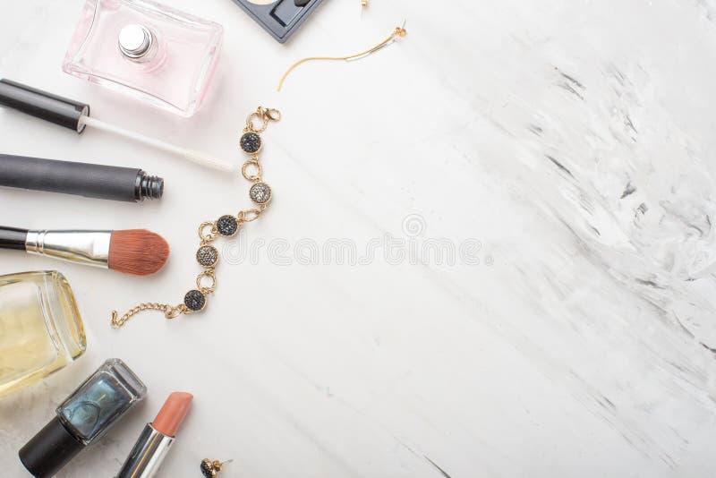 Reeks professionele schoonheidsmiddelen, make-uphulpmiddelen en toebehoren op een witte marmeren achtergrond met exemplaarruimte  stock afbeelding
