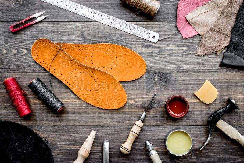 Reeks schoenmakershulpmiddelen op bruine houten bureau hoogste mening als achtergrond royalty-vrije stock afbeelding