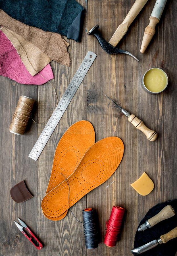 Reeks schoenmakershulpmiddelen op bruine houten bureau hoogste mening als achtergrond stock foto