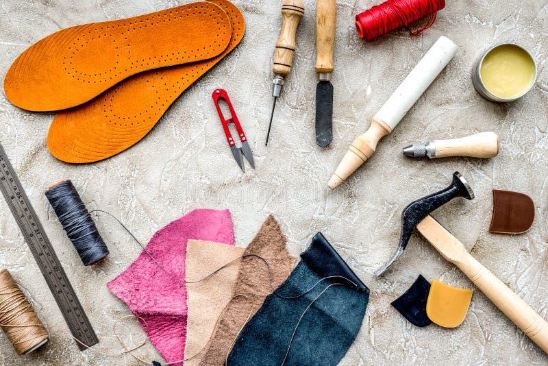 Reeks schoenmakershulpmiddelen op grijze van het steenbureau hoogste mening als achtergrond royalty-vrije stock foto