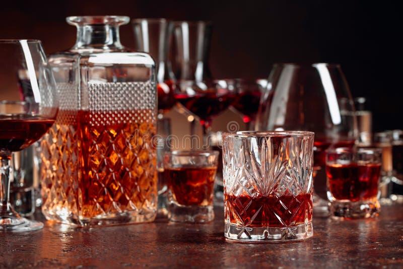 Reeks sterke alcoholische dranken in glazen op een bruine achtergrond stock foto