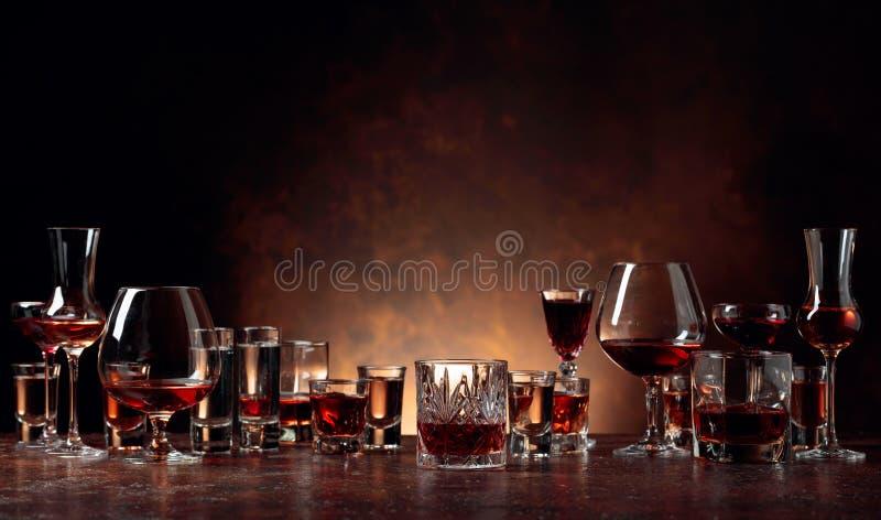 Reeks sterke alcoholische dranken in glazen op een bruine achtergrond royalty-vrije stock afbeelding
