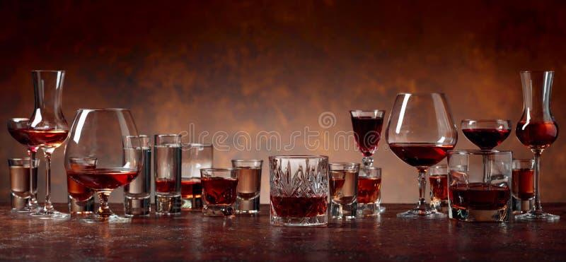 Reeks sterke alcoholische dranken in glazen op een bruine achtergrond royalty-vrije stock foto