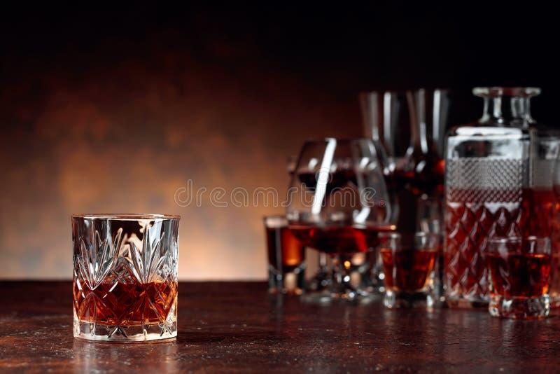 Reeks sterke alcoholische dranken in glazen op een bruine achtergrond stock afbeeldingen