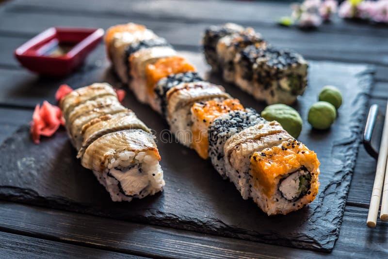 Reeks sushi en werktuigen op een zwarte houten achtergrond royalty-vrije stock foto