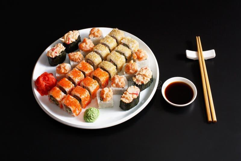 Reeks sushimaki en broodjes bij zwarte achtergrond royalty-vrije stock afbeelding