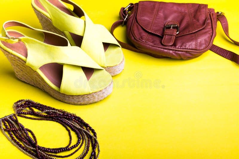 Reeks Toebehoren van Vrouwen` s Dingen aan Zomer Bruin Zak Geel Platform Sandals, Halsband Vlak leg royalty-vrije stock foto's