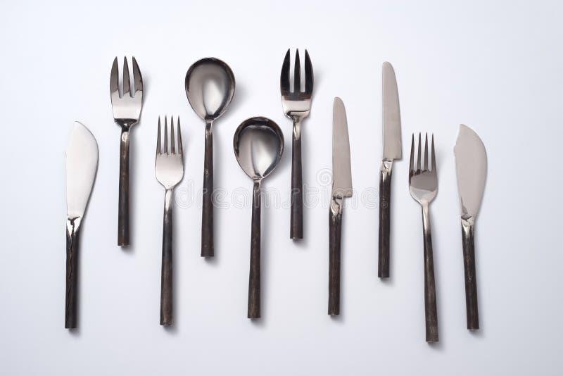 Reeks uitstekende metaallepels, vorken en messen op een grijze achtergrond met ruimte voor tekst Vlak leg stock foto
