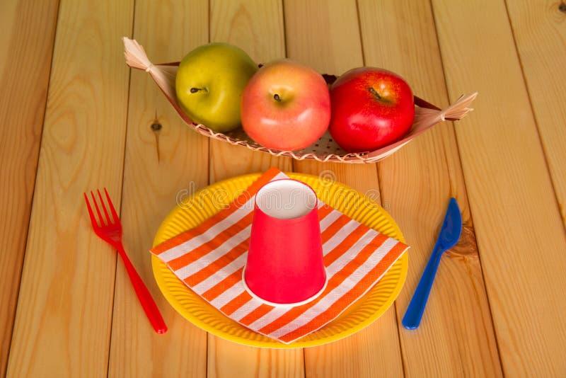 Reeks van beschikbaar plastic vaatwerk, appelen in mand, op lijst royalty-vrije stock foto