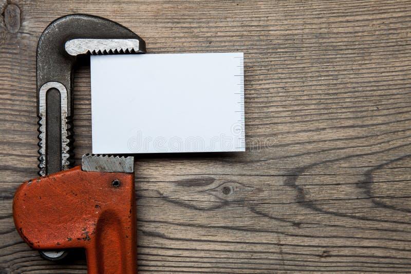 Reeks van de hulpmiddelenmontage van het pijpenloodgieterswerk en adreskaartje op de houten achtergrond royalty-vrije stock afbeelding