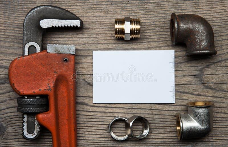 Reeks van de hulpmiddelenmontage van het pijpenloodgieterswerk en adreskaartje op de houten achtergrond royalty-vrije stock foto
