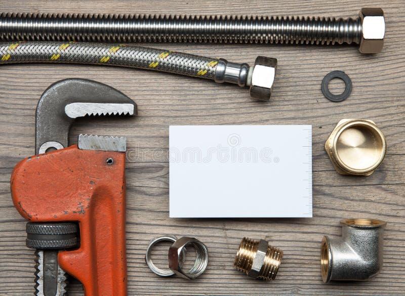 Reeks van de hulpmiddelenmontage van het pijpenloodgieterswerk en adreskaartje op de houten achtergrond stock fotografie