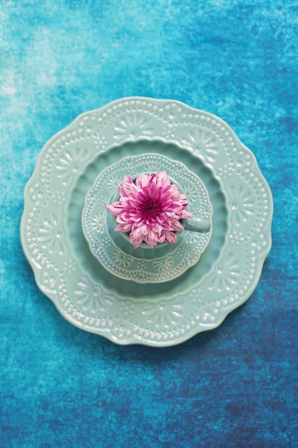 Reeks van decoratieve porseleinschotels en purpere bloem stock fotografie