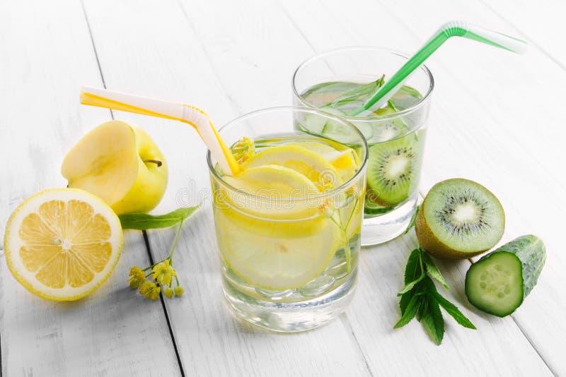 Reeks van dieetdranken, mineraalwater in een glas, verse groene kiwi, munt en komkommer, citroen en gele appel Ontgifting en royalty-vrije stock foto's