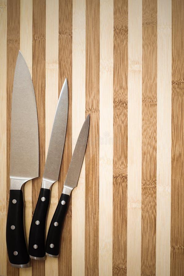 Reeks van drie professionele kokende messen op scherpe raad stock foto's
