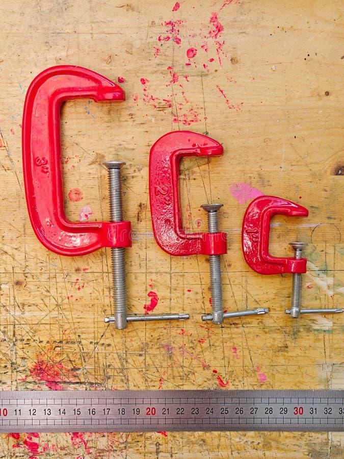 Reeks van drie rode metaalc klemmen en heerser stock afbeelding