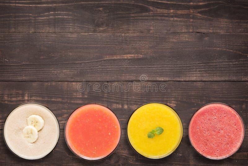 Reeks van fruit smoothie en sap in glazen op houten achtergrond royalty-vrije stock afbeeldingen