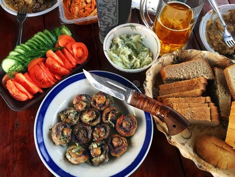 Reeks van gebraden paddestoelen, tomaat, komkommer en bier op een houten lijst royalty-vrije stock afbeelding