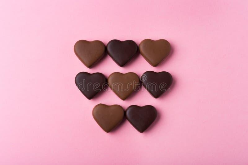 Reeks van het hart van chocoladesnoepjes op roze achtergrond wordt gevormd die stock foto's