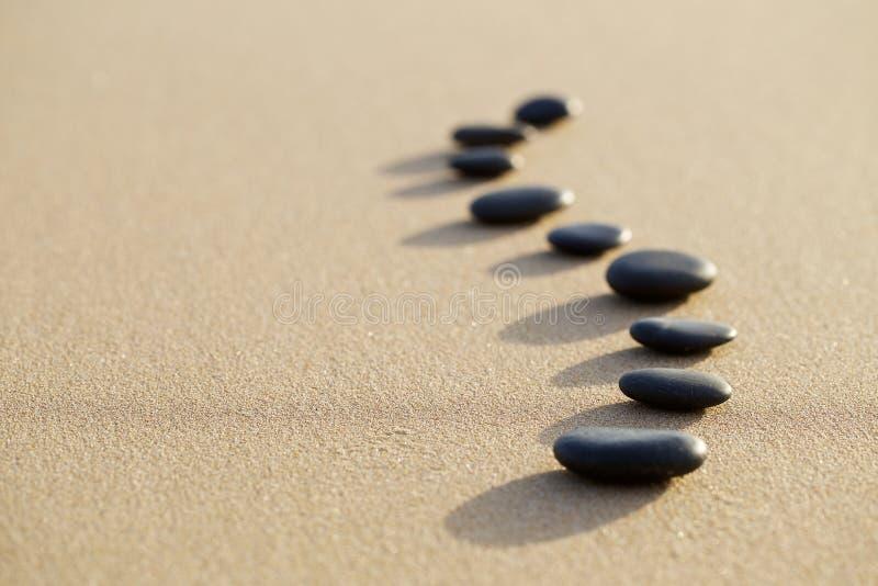 Reeks van hete steen op wit zand kalm strand in backbonevorm Sel royalty-vrije stock afbeelding
