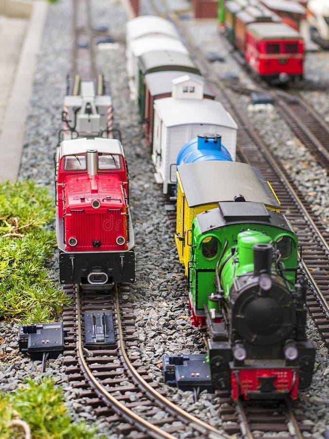Reeks van rode elektrische modelspoorweglocomotief en lay-out met een post en gehele scène met eigenschappen stock afbeeldingen