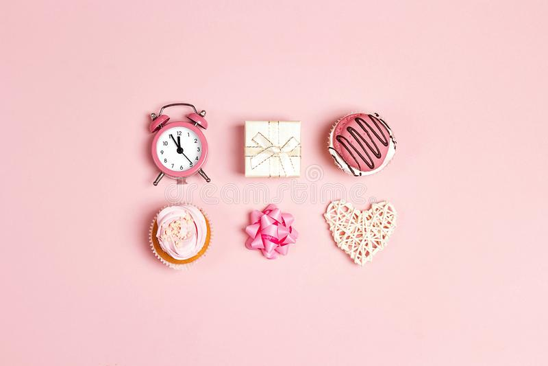 Reeks van smakelijk cupcakes, wekker, gift en hart op roze pastelkleurachtergrond royalty-vrije stock afbeelding
