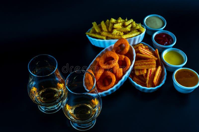 Reeks van snacks met verschillende onderdompelingen en één enkel mout in een glas, stock afbeelding