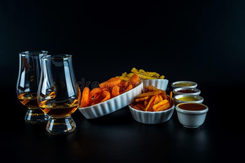 Reeks van snacks met verschillende onderdompelingen en één enkel mout in een glas, stock foto