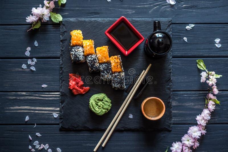 Reeks van sushi en kersentak op een zwarte lijst stock afbeelding