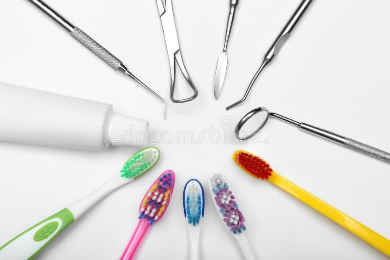 Reeks van tandarts\ 's hulpmiddelen, tandenborstels en deeg op witte achtergrond stock foto