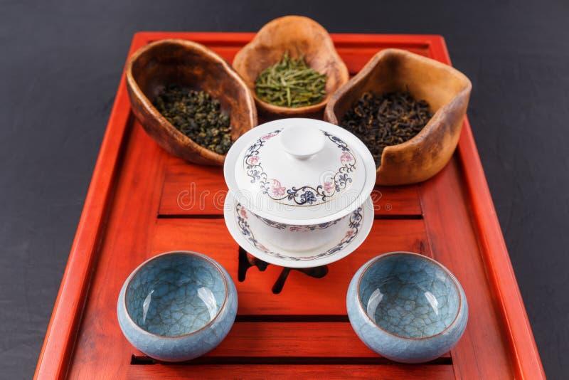 Reeks van theepot, drie soorten thee en vier kommen stock afbeelding