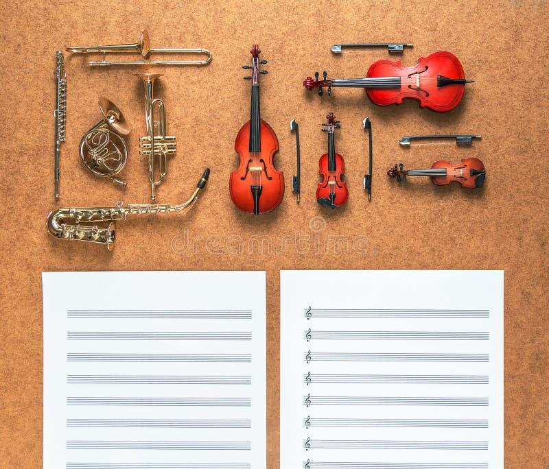Reeks van vijf gouden messingswind en vier instrumenten van het koord muzikale orkest en bladmuziek die dichtbij het liggen Het c royalty-vrije stock foto's