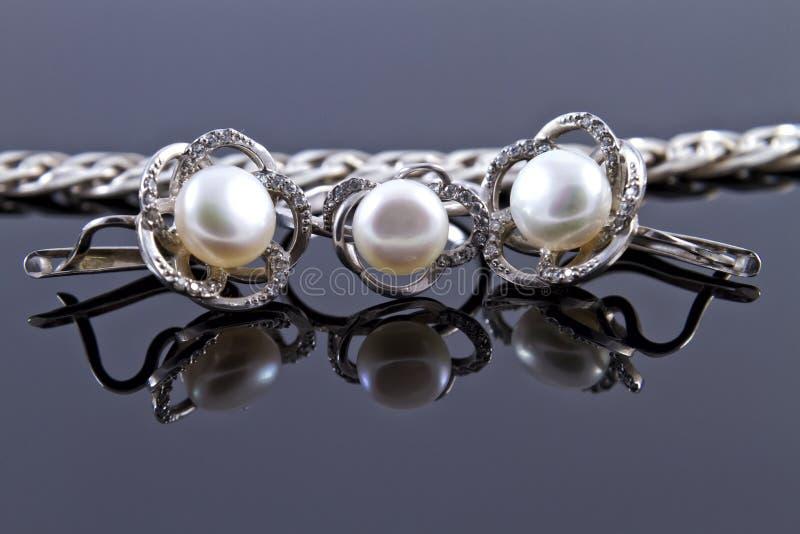 Reeks van zilveren oorringen en een ring stock afbeelding