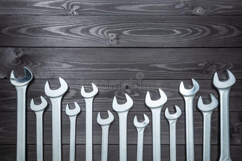 Reeks verchroomde moersleutels op een donkere houten werkbank Hoogste mening, exemplaarruimte stock afbeelding