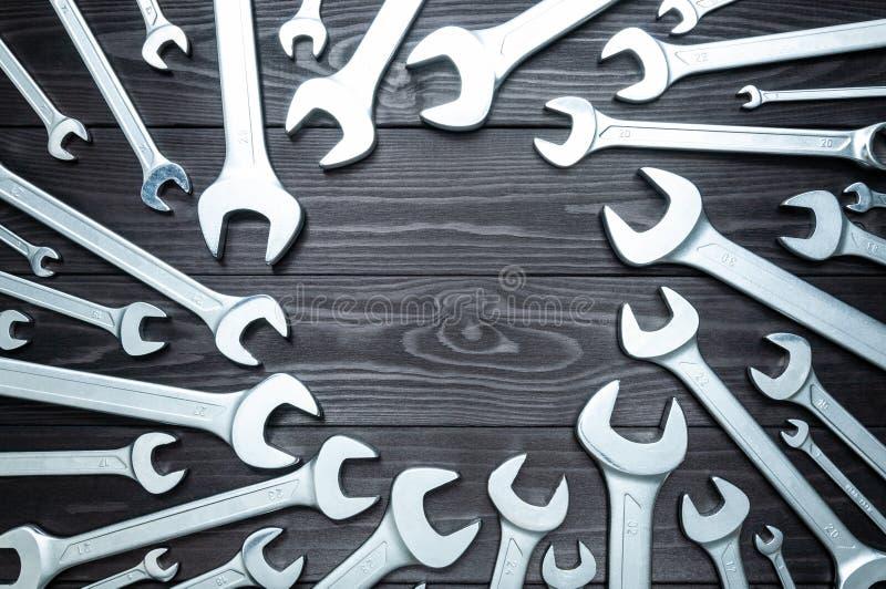 Reeks verchroomde moersleutels op een donkere houten werkbank Hoogste mening, exemplaarruimte stock fotografie