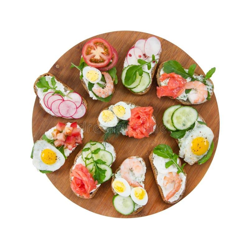 Reeks verscheidenheids kleine sandwiches op ronde scherpe geïsoleerde raad stock afbeeldingen